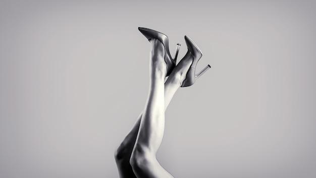 Pernas femininas perfeitas de salto alto. pernas bem torneadas, uma garota de sapatos de salto alto. preto e branco.