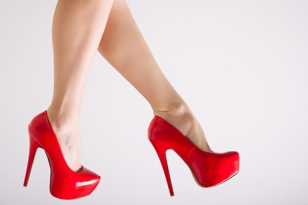 Pernas femininas perfeitas de salto alto vermelho isolado no fundo branco