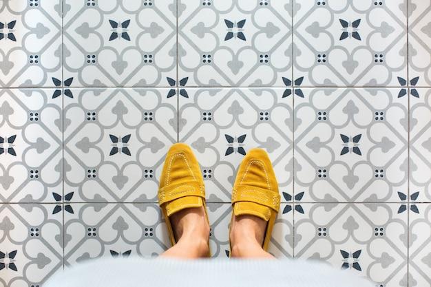Pernas femininas, pés em sapatos amarelos em um piso de ladrilho de mosaico. vista de cima, selfie plana em um fundo vintage sem costura, copie o espaço