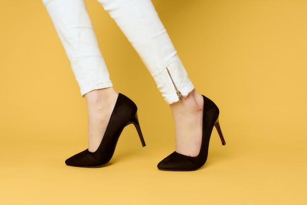 Pernas femininas sapatos pretos da moda aparência atraente jeans branco fundo amarelo