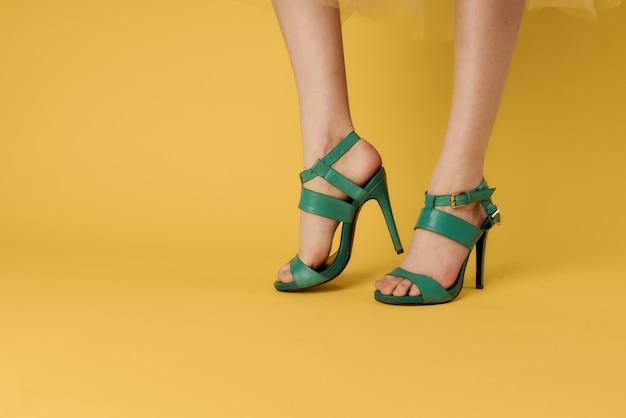 Pernas femininas sapatos verdes sapatos da moda amarelo fundo