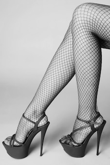 Pernas femininas sexy com sapatos de striptease vermelhos de salto alto e meias arrastão