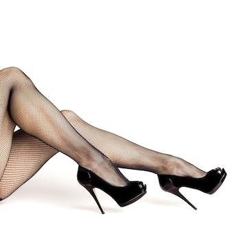Pernas femininas sexy com sapatos pretos de salto alto e meias arrastão isoladas no fundo branco