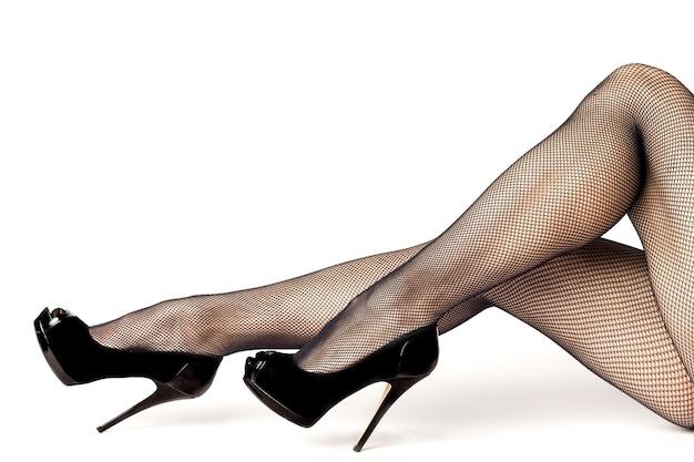 Pernas femininas sexy com sapatos pretos de salto alto e meias arrastão
