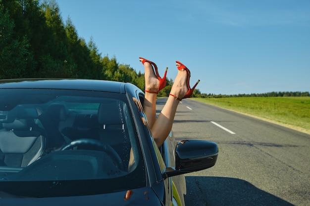 Pernas femininas sexy com sapatos vermelhos saindo da janela de vento de um carro