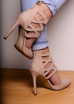 Pernas femininas sexy em sapatos de camurça de salto alto com cordão