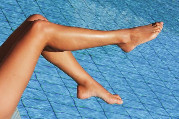 Pernas femininas sexy na água azul da piscina