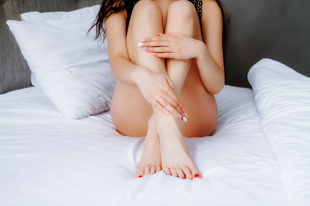 Pernas femininas suaves na cama. pernas das mulheres após a depilação a laser.