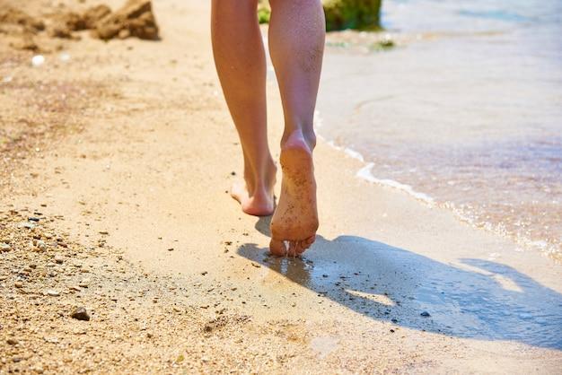 Pernas femininas vão ao longo da costa do mar em um dia ensolarado.