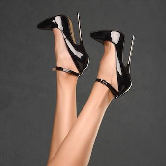 Pernas finas de mulher em um sapato fetiche com salto extremamente alto. tema bdsm.