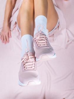 Pernas finas elegantes de menina em sapatos esporte rosa