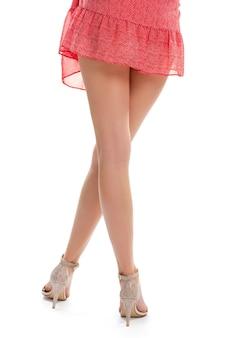 Pernas finas em sapatos de salto. vestido vermelho e salto bege. sapatos de noite casuais de menina. siga a tendência.