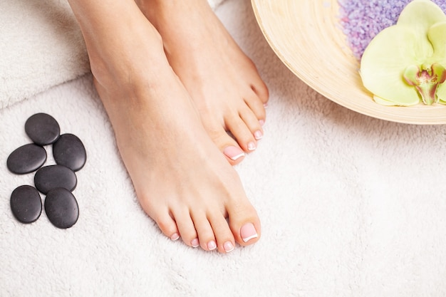 Pernas finas femininas de beleza após terapia de spa em fundo branco. Foto Premium