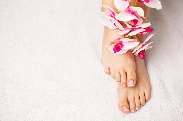 Pernas finas femininas de beleza após terapia de spa em fundo branco.