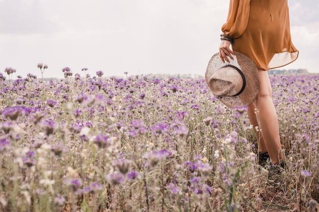 Pernas finas. mãos da menina segurando um chapéu de palha