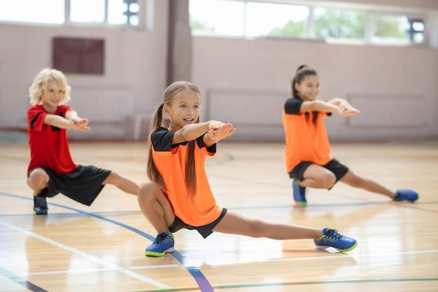 Pernas fortes. três crianças se exercitando na academia e fazendo investidas para a esquerda
