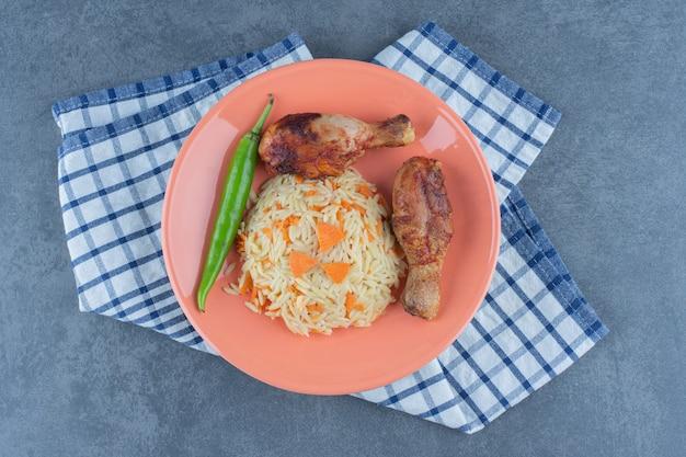 Pernas grelhadas e arroz temperado no prato laranja.