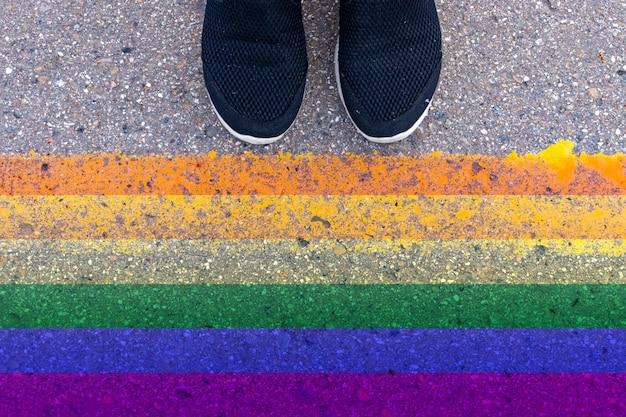 Pernas humanas cortadas em sapatos pretos, de pé no asfalto na frente da bandeira colorida arco-íris lgbt, identidade de gênero e autodeterminação