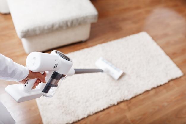 Pernas humanas e uma escova turbo branca de um aspirador de pó sem fio limpam o carpete da casa
