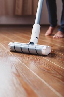 Pernas humanas e uma escova turbo branca de um aspirador sem fio limpam o parquete da casa. tecnologias modernas para limpeza.