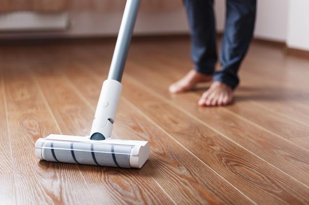Pernas humanas e uma escova turbo branca de um aspirador sem fio limpam o parquete da casa.