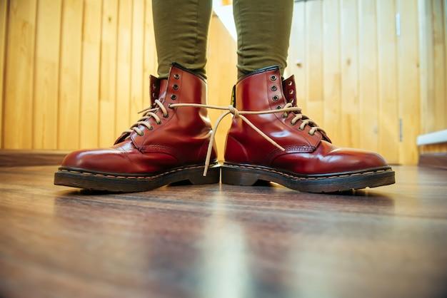 Pernas humanas em elegantes botas vermelhas brilhantes com atacadores brancos grossos amarrados juntos, close-up. dia da mentira, brincadeiras e diversão
