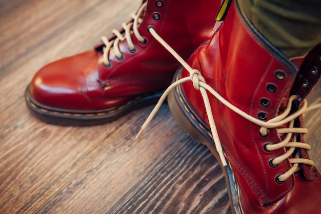 Pernas humanas em elegantes botas vermelhas brilhantes com atacadores brancos grossos amarrados juntos em madeira