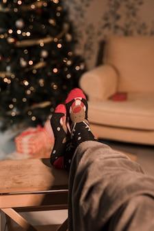 Pernas humanas em meias engraçadas perto de árvore de natal e sofá