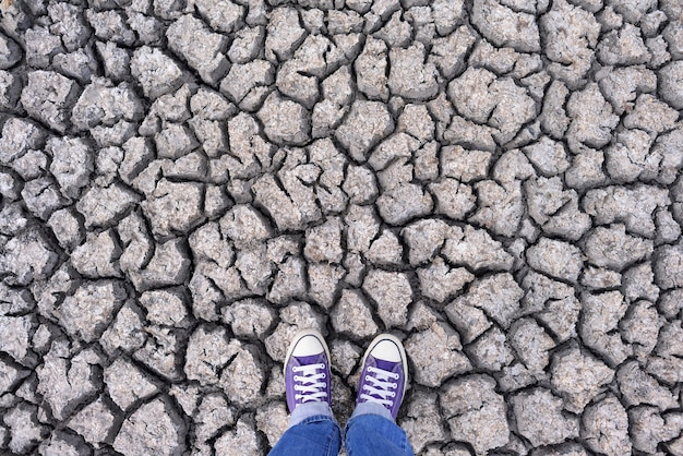 Pernas humanas em tênis e jeans em pé na terra rachada seca, plano de fundo