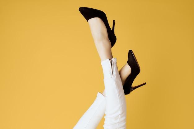 Pernas invertidas femininas e sapatos pretos jeans branco isolado fundo amarelo