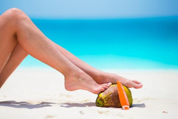 Pernas lisas bronzeadas femininas com suncream e coco na praia branca