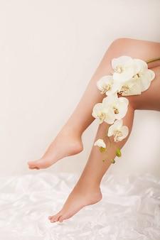 Pernas longas da mulher segurando lindas flores