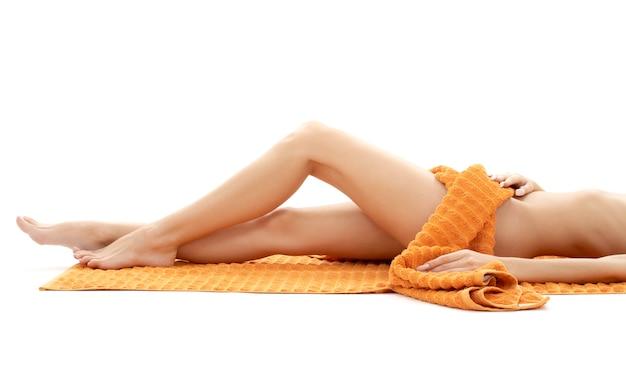 Pernas longas de senhora relaxada com toalha laranja sobre branco