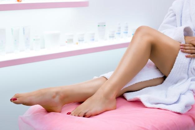 Pernas longas de uma menina em um salão de beleza. depilação a laser para mulheres. cuidados com a pele. pedicure bem cuidada nos pés.