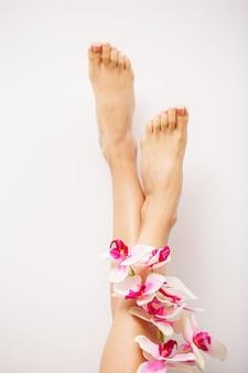 Pernas longas de uma mulher com uma manicure fresca e flores da orquídea
