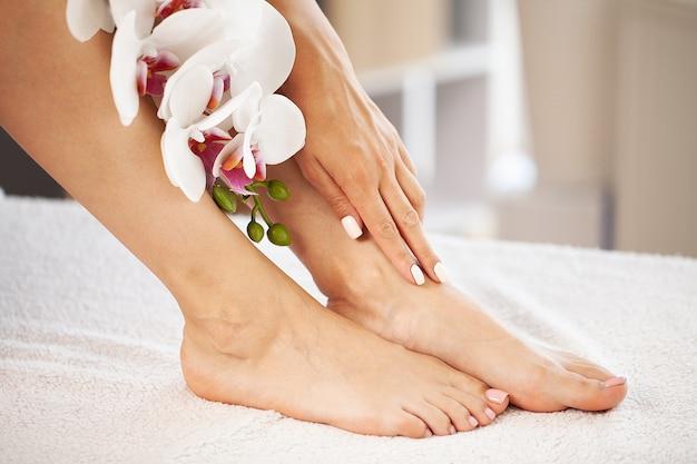 Pernas longas de uma mulher com uma manicure fresca e flores da orquídea.