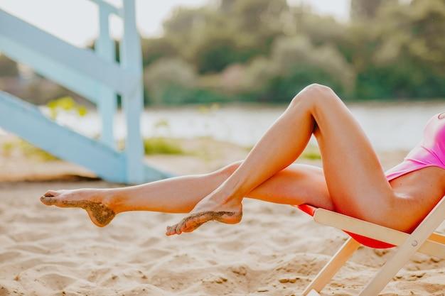 Pernas longas e finas de mulher em biquíni rosa, sentado na cadeira na praia de areia