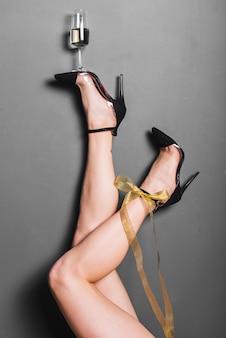 Pernas longas em saltos segurando a flauta de champanhe