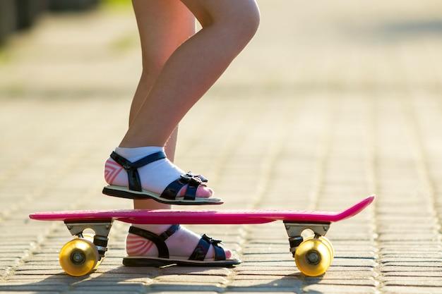 Pernas magras de criança em meias brancas e sandálias pretas no plástico rosa skate no verão ensolarado brilhante turva cópia pavimento de espaço. atividades ao ar livre e conceito de estilo de vida saudável.