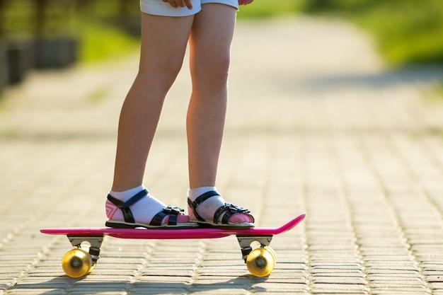 Pernas magro de menina em meias brancas e sandálias pretas em pé na calçada em plástico rosa skate no verão ensolarado brilhante. atividades ao ar livre e conceito de estilo de vida saudável.