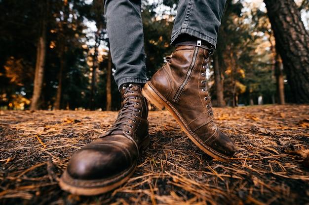 Pernas masculinas demonstrando couro marrom botas elegantes na floresta de outono.