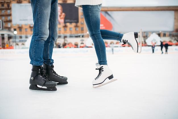 Pernas masculinas e femininas de patins, amor casal na pista. patinação de inverno ao ar livre, lazer ativo, patinação no gelo
