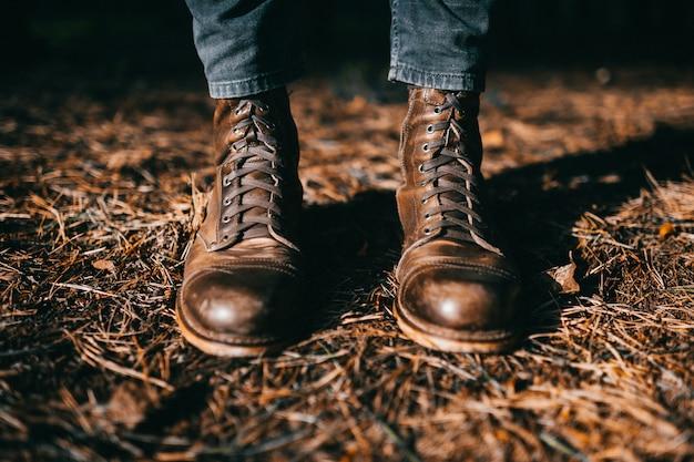 Pernas masculinas em botas de couro na moda em pé no outono folhas.