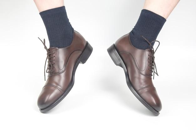 Pernas masculinas em meias e sapatos clássicos de couro marrom em um branco