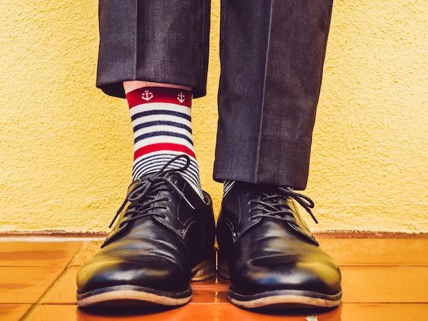 Pernas masculinas, sapatos elegantes e meias coloridas