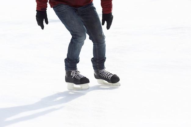 Pernas montam um cara patinando na pista de gelo