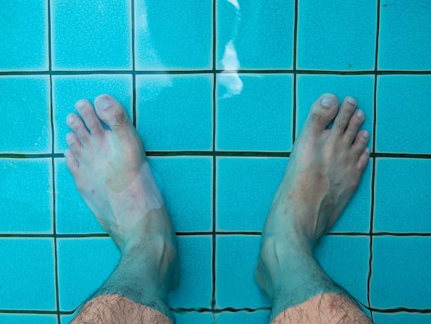 Pernas na água da piscina. fundo de viagem de verão