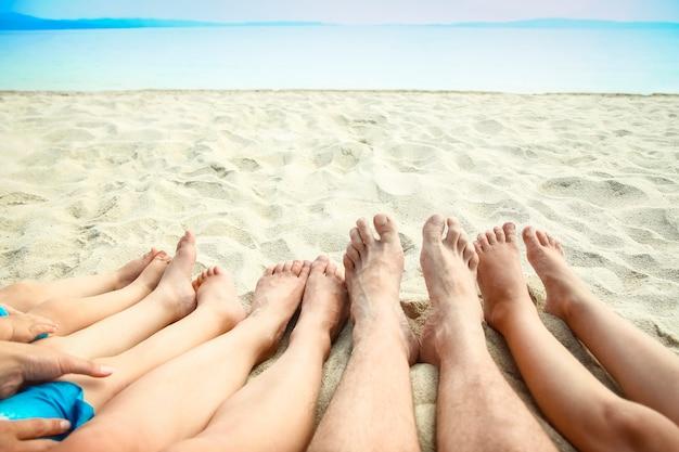 Pernas na areia do mar