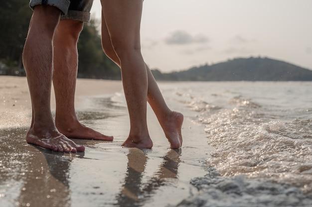 Pernas na praia um jovem casal apaixonado se abraçando e se beijando na praia ao sol dois amantes