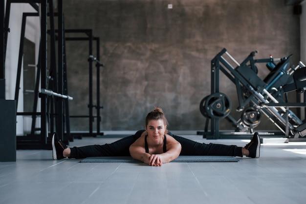 Pernas nas laterais. foto de uma linda mulher loira na academia no fim de semana